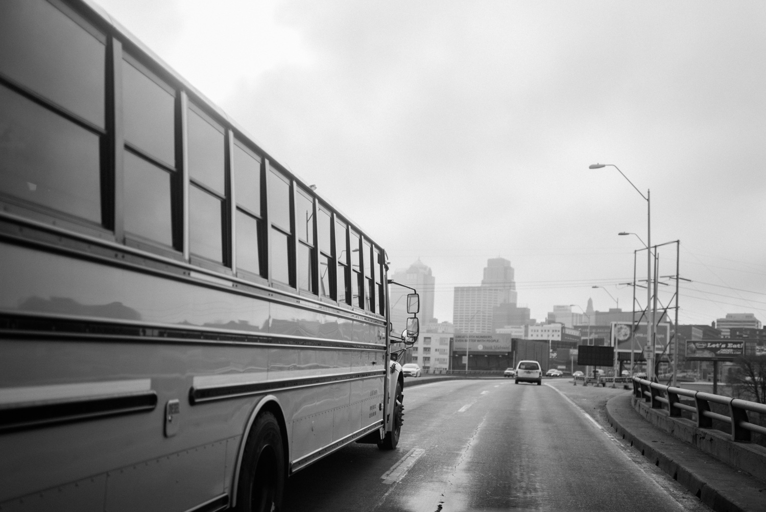 School Bus driving toward Kansas City skyline in black and white
