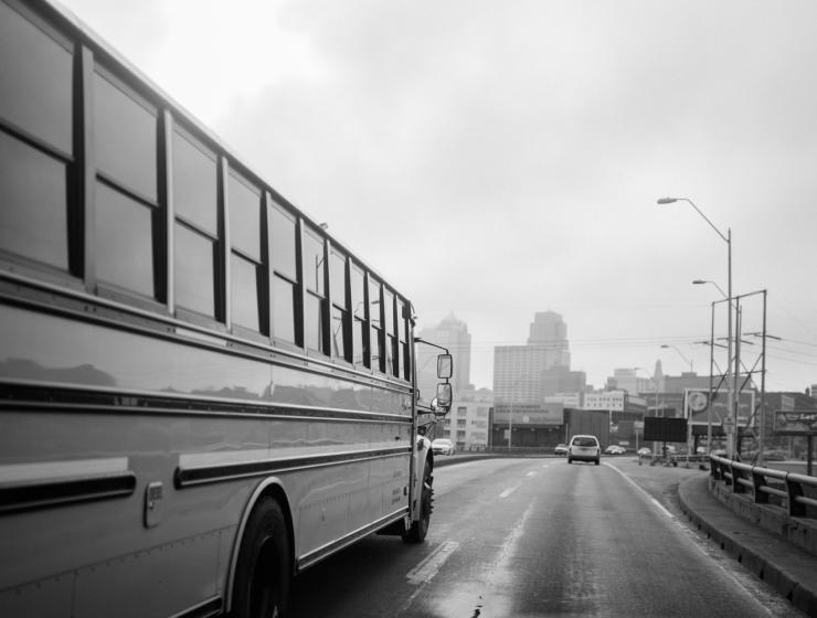 School Bus driving toward Kansas City skyline in black and white